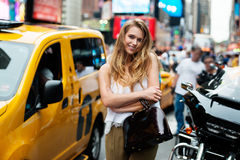 Beautiful fashionable young woman with yellow taxi cab at busy New York City Street. Cheerful blonde girl smiling in the city stre. Et and holding bag wearing Stock Image