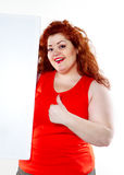 The beautiful fat, big sensuality woman with red lipstick and with red t-shirts holding the white bilboard. On the white background. When she hold bilboard the Stock Photography
