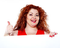 The beautiful fat, big sensuality woman with red lipstick and with red t-shirts holding the white bilboard. On the white background. When she hold bilboard the Royalty Free Stock Image