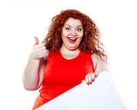 The beautiful fat, big sensuality woman with red lipstick and with red t-shirts holding the white bilboard. On the white background. When she hold bilboard the Royalty Free Stock Images