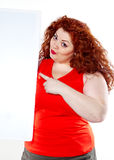 The beautiful fat, big sensuality woman with red lipstick and with red t-shirts holding the white bilboard. On the white background. When she hold bilboard the Royalty Free Stock Photo