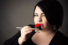 Beautiful fat woman face with sushi and rolls royalty free stock photography