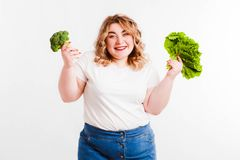 Beautiful fat young woman with bright emotions on a light gray background. Concept of diet. Space for text. Design royalty free stock images