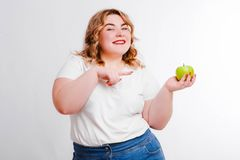 Beautiful fat young woman with bright emotions on a light gray background. Concept of diet. Space for text. Design royalty free stock photography