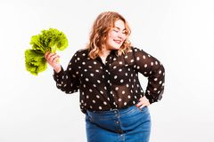 Beautiful fat young woman with bright emotions on a light gray background. Concept of diet. Space for text. Design stock photography