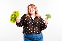 Beautiful fat young woman with bright emotions on a light gray background. Concept of diet. Space for text. royalty free stock image
