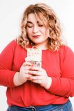 Beautiful fat young woman with bright emotions on a light gray background. Concept of diet. Space for text. royalty free stock images