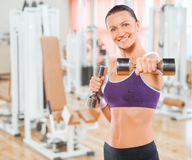 Beautiful feamale exercising with weights in gym Royalty Free Stock Photography