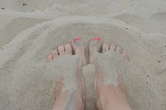 Beautiful feet buried in the sand. Women`s healthy feet in the sand with pink nail polish relaxing in nature letting go of stress Stock Image