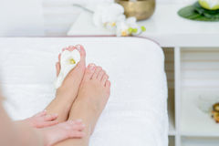 Beautiful feet with french pedicure and flowers Stock Photos