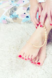 Beautiful feet and hands. With red nails and pearls Stock Image