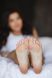 Beautiful feet, lying in the bed of a young woman royalty free stock image