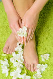 Beautiful feet with pedicure and flowers at green background Royalty Free Stock Photography