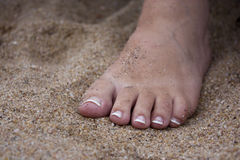 Beautiful feet on see sand Stock Images