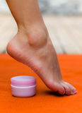 Beautiful feet standing on her toes with a pot of cream, pink color of the pot and orange background Royalty Free Stock Photography