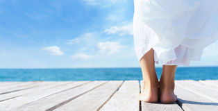 Beautiful feet of a woman in white dress on a wooden pier.  Sea Stock Photos
