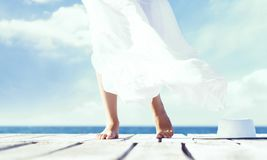 Beautiful feet of a woman in white dress on a wooden pier. Sea and sky background. Beautiful feet of a woman in white dress on a wooden pier.  Sea and sky Royalty Free Stock Photography