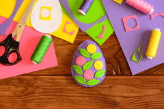 Beautiful felt Easter egg decor with flowers, scissors, thread, needle, paper template, colored felt sheets and scraps Stock Photo