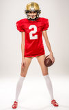 Beautiful female american football player. In helmet posing with ball on grey Royalty Free Stock Image