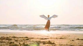 Beautiful female angel walking barefoot toward the sea at sunset. Beautiful female angel walking barefoot from camera toward the sea at sunset, rear view stock photo