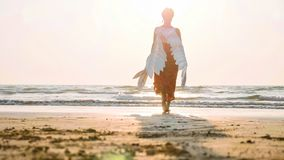 Beautiful female angel walking barefoot toward the sea at sunset. Beautiful female angel walking barefoot from camera toward the sea at sunset, rear view stock photography