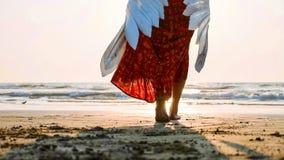 Beautiful female angel walking barefoot toward the sea at sunset. Beautiful female angel walking barefoot from camera toward the sea at sunset, rear view royalty free stock photos