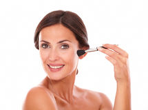 Beautiful female applying facial care product Stock Images
