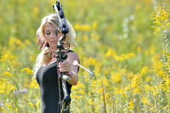 Beautiful female archer shoots an arrow. Stunning young blonde archer (female) shooting a bow in a black tank top - arrow in frame leaving bow Stock Photos