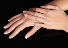 Beautiful female arms with ideal french manicure on black background. Care about female hands, healthy soft skin. Spa Royalty Free Stock Photos