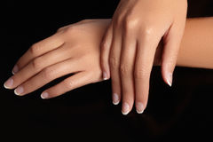 Beautiful female arms with ideal french manicure on black background. Care about female hands, healthy soft skin. Spa Stock Images