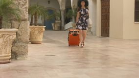 Beautiful female arrives in exotic city on vacation, carrying luggage to hotel. Stock footage stock video footage