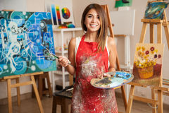 Beautiful female artist in her studio. Portrait of a gorgeous female artist working on several art projects on her studio Stock Photography