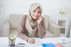 Beautiful female asian student with hijab doing homework. Portrait of beautiful female asian student with hijab doing homework royalty free stock images