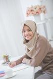 Beautiful female asian student with hijab doing homework Stock Photo
