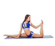Beautiful female athlete doing gymnastic split. Isolated on white Stock Photo