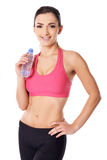 Beautiful female athlete drinking water. Beautiful shapely female athlete drinking pure bottled water to rehydrate after completing her exercises Stock Photography