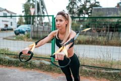 Beautiful female athlete, girl wrung on loops, gymnastics, muscle stretching, flexibility and plasticity training, in stock photos