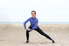 Beautiful female athlete in stretch on beach Stock Photos