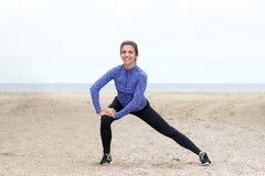 Beautiful female athlete in stretch on beach. Full body portrait of beautiful female athlete in stretch on beach Stock Photos