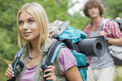 Beautiful female backpacker looking away with man in background at forest Royalty Free Stock Images