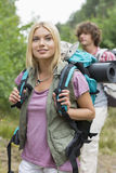 Beautiful female backpacker looking away with man standing in background at forest Stock Image
