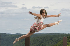 Beautiful female ballerina or dancer leaps outdoors Stock Image