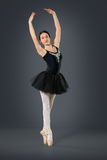 Beautiful female ballet dancer on a grey background. Royalty Free Stock Photography