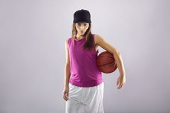 Beautiful female basketball player on grey background Royalty Free Stock Photography