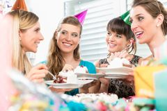 Beautiful female best friends sharing a birthday cake. Beautiful female best friends with positive thinking and sense of humor sharing a birthday cake during a stock photos