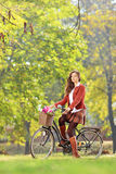 Beautiful female on a bicycle in a park Royalty Free Stock Image