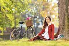 Beautiful female with bicycle sitting in a park and looking at c Stock Images