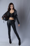Beautiful female biker wearing a leather jacket. In studio Royalty Free Stock Photography
