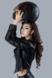 Beautiful female biker wearing a leather jacket. In studio Royalty Free Stock Images