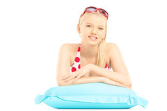 Beautiful female in bikini lying on a swimming mattress Stock Images